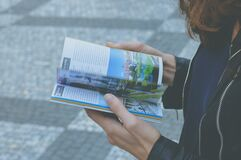 Woman in Black Zipped Jacket Hoding White and Blue Book Royalty Free Stock Photos