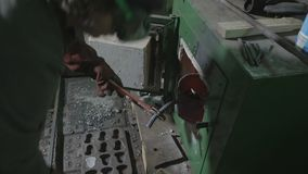 Woman blacksmith collecting aluminum and placing in into a special furnace to heat melt and recycle it in an workshop -. Woman blacksmith collecting aluminum and stock footage