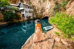 Woman in Blagaj Buna. Woman in dress and hat walking to the river in Blagaj Buna Royalty Free Stock Photography