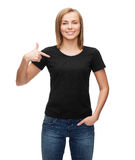 Woman in blank black t-shirt. T-shirt design, happy people concept - smiling woman in blank black t-shirt pointing her finger at herself Royalty Free Stock Photography