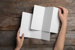 Woman with blank brochures on wooden background, above view. stock images
