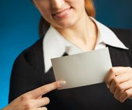 Woman with blank business-card. Young attractive secretary or businesswoman with sign or blank business-card, smiling. Focus on card Stock Photo