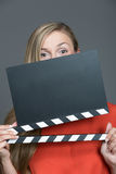 Woman with a blank clapper slate. Hiding the lower portion of her face as she holds it up for the camera to record the information and sound during filming and Royalty Free Stock Photography