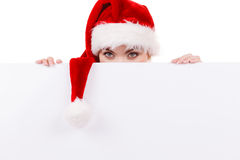 Woman with blank empty banner board. Christmas. Woman holding banner sign peeking over edge of blank empty billboard with copy space for text. Girl in santa Stock Photography