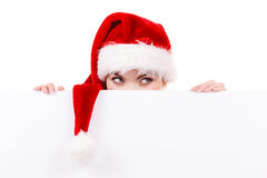 Woman with blank empty banner board. Christmas. Woman holding banner sign peeking over edge of blank empty billboard with copy space for text. Girl in santa Stock Image