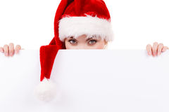 Woman with blank empty banner board. Christmas. Woman holding banner sign peeking over edge of blank empty billboard with copy space for text. Girl in santa Royalty Free Stock Photos