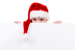 Woman with blank empty banner board. Christmas. Woman holding banner sign peeking over edge of blank empty billboard with copy space for text. Girl in santa Royalty Free Stock Image