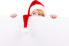 Woman with blank empty banner board. Christmas. Woman holding banner sign peeking over edge of blank empty billboard with copy space for text. Girl in santa Stock Photo
