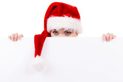 Woman with blank empty banner board. Christmas. Woman holding banner sign peeking over edge of blank empty billboard with copy space for text. Girl in santa Royalty Free Stock Photo