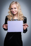 Woman with Blank Notice. Attractive blond woman holding a blank paper notice Royalty Free Stock Images