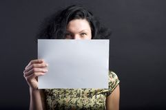 Woman with blank paper. Brunette woman holding blank sheet of paper Stock Photo