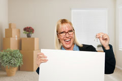 Woman with Blank Sign and House Key in Empty Room with Packed Mo Stock Images