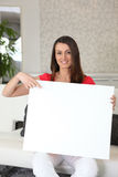 Woman with a blank sign. Woman sitting on a sofa with a blank sign on her lap Royalty Free Stock Photography