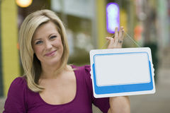 Woman with blank white sign for text. Pretty blond woman holding up a blank white sign with urban background Stock Photos