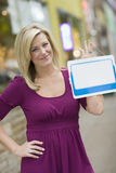 Woman with blank white sign for text. Pretty blond woman holding up a blank white sign with urban background Stock Images