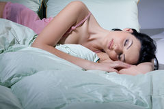Woman, Blanket And Pillows. Young beautiful woman lying with down pillows and blanket stock image