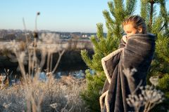 Woman in blanket standing near conifer tree in countryside royalty free stock photography