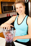 Woman blender. Young woman with a blender filled with berries stock photos