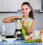 Woman with blender at kitchen Stock Images