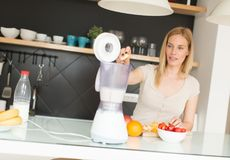 Woman blending fruits. And making smoothie royalty free stock photography