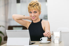 Woman blending her coffee while using a computer in a bar Stock Image