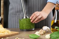 Woman blending pesto sauce in bowl at table. Closeup royalty free stock photo