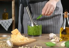 Woman blending pesto sauce in bowl at table. Closeup royalty free stock photos