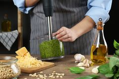 Woman blending pesto sauce in bowl at table. Closeup stock photo