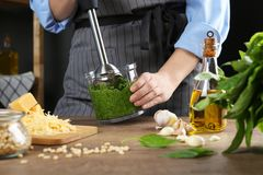 Woman blending pesto sauce in bowl at table. Closeup stock photography