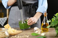 Woman blending pesto sauce in bowl at table. Closeup royalty free stock image