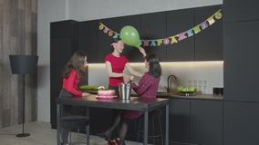 Woman with blindfold groping mom at birthday party. Cheerful adult female enjoying celebration of Birthday in narrow circle with mother and good friend in stock video footage