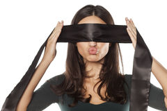 Woman blindfolding herself Royalty Free Stock Photos
