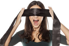 Woman blindfolding herself Royalty Free Stock Photo