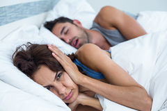Woman blocking ears with hands while man snoring on bed. Portrait of women blocking ears with hands while men snoring on bed royalty free stock photography