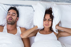 Woman blocking ears while man snoring on bed Royalty Free Stock Image