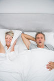 Woman blocking her ears because of partners snoring. At home in bed Stock Images