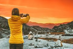 Woman blogger taking photo by smartphone of sunset mountains. Landscape Travel Lifestyle concept adventure vacations in Norway outdoor modern technology Stock Photography