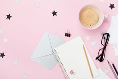 Woman blogger working desk with coffee, eyeglasses, pencil, envelope and clean notebook on pink table top view. Flat lay. royalty free stock photos