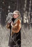 Woman blond in autumn in fur coat with owl on hand first snow. B Royalty Free Stock Photography
