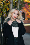 Woman with blond curly hair in park. Beautiful Portrait of sensual young model wearing a coat and grey scarf. With glamour red lips make-up, eye arrow makeup Stock Images