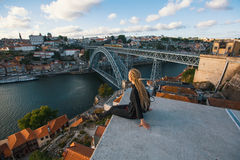 Woman with blond dreadlocks on the viewing platform opposite the Dom Luis I bridge across the Douro river in Porto Stock Photo