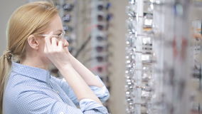 Woman blond girl is choosing new eyeglasses in optics. Woman blond girl selects points in front of the mirror optics stock video footage