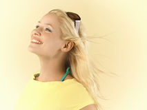 Woman With Blond Hair Blowing In Wind. Closeup side view of a young woman with blond hair blowing in wind against yellow background Stock Photography