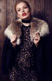 Woman with blond hair and bright makeup wearing  luxurious fur coat Royalty Free Stock Photos
