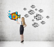 Woman with blond hair is coloring fish Royalty Free Stock Photo