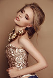 Woman with blond hair in elegant golden dress and luxurious necklace Royalty Free Stock Photo