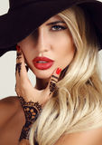 Woman with blond hair with evening makeup and henna tattoo on hands stock photo