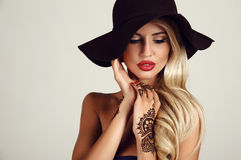 Woman with blond hair with evening makeup and henna tattoo on hands Royalty Free Stock Photo