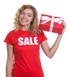 Woman with blond hair and gift in a sales-shirt Stock Image