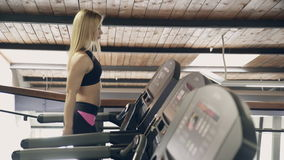 A woman with blond hair in the gym walks along the treadmill. stock video footage